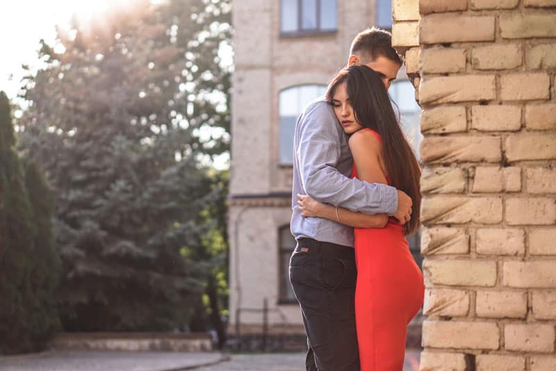 couple hugging by the wall outdoor