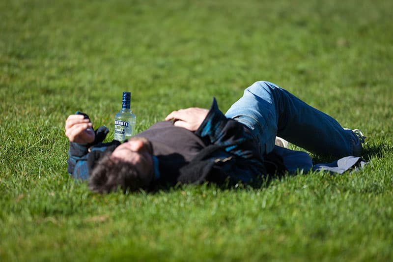 drunk man laying on the grass