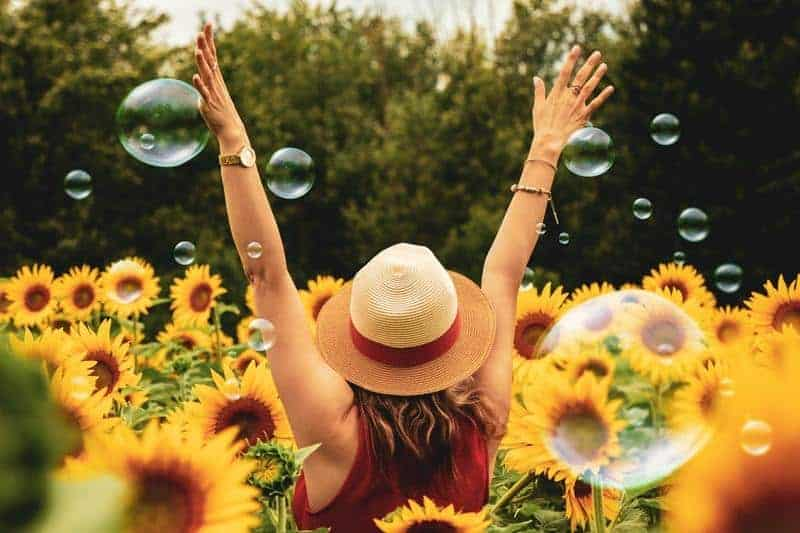 happy woman standing in the flower field