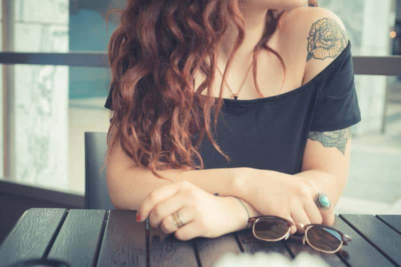 hipster woman with red curly hair and tattoo on her arm
