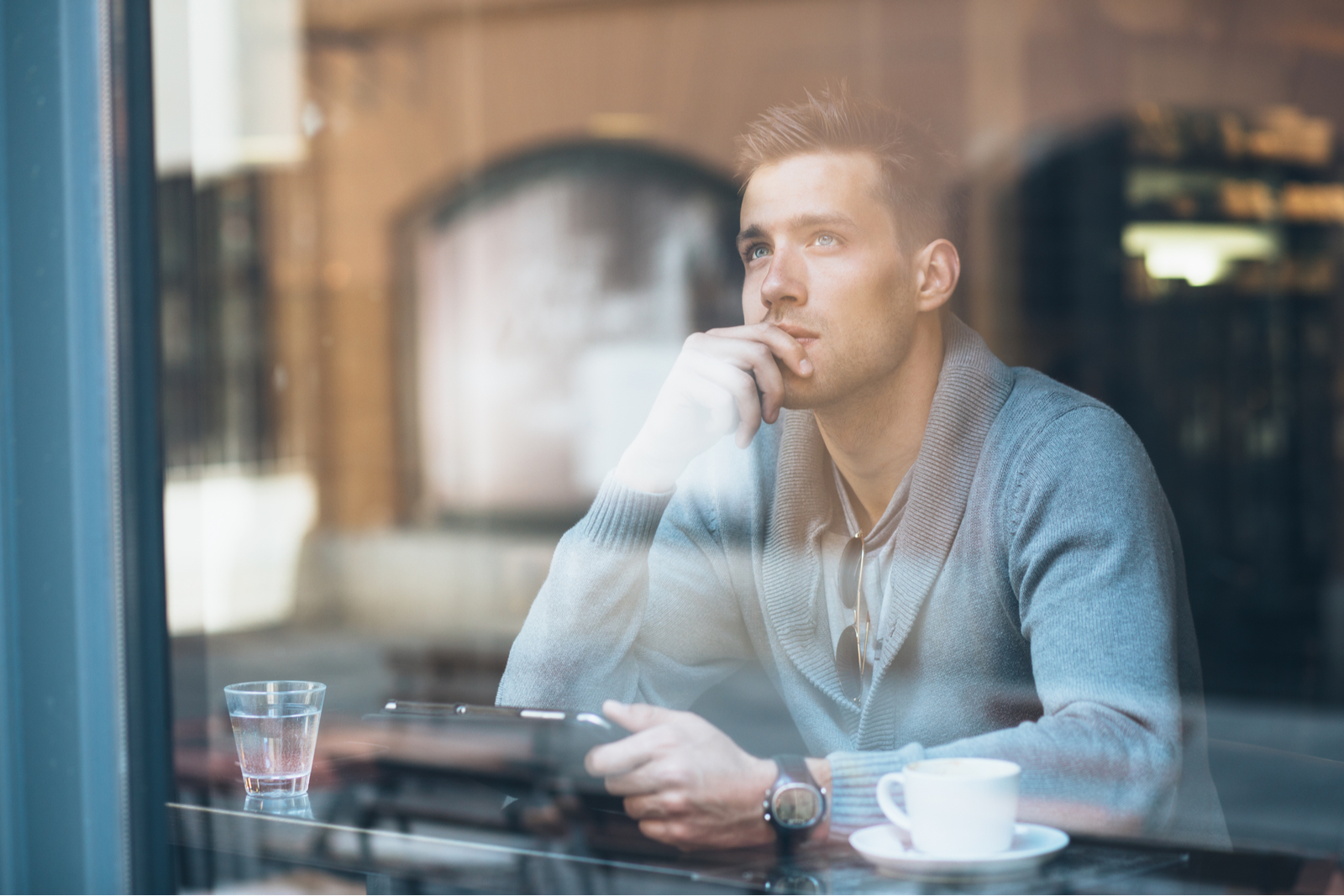 in a cafe by the window behind the bar sits a man with a tablet in his hand and thinks