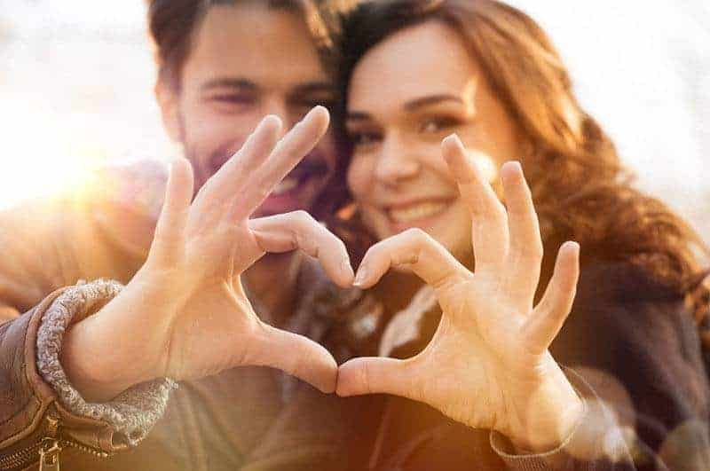 man and woman making heart sign of hands