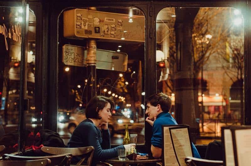 man carefully watching woman at cafe