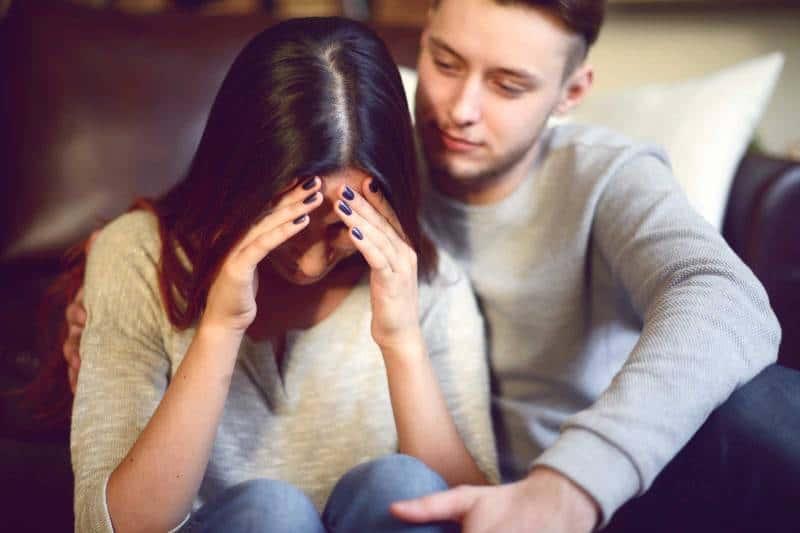 man comforting crying woman at home