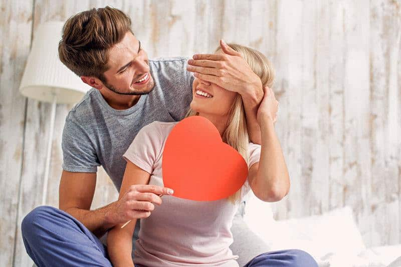 man covering his girlfriend eyes with hand