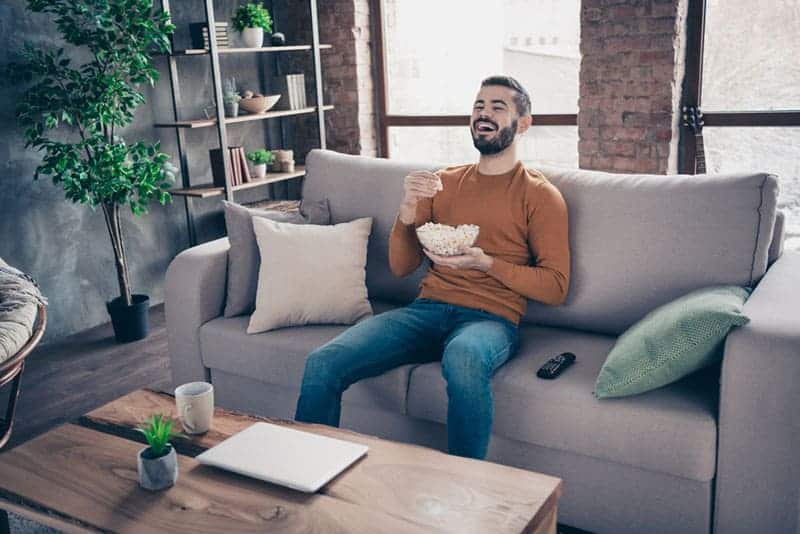 man eating popcorn and laughing while watching a TV