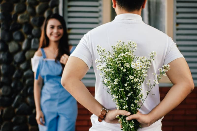 man holding flowers behind while smiling woman standing in front of him