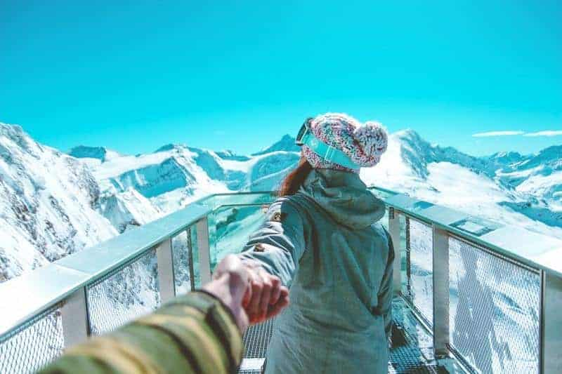 man holding woman hand on mountain
