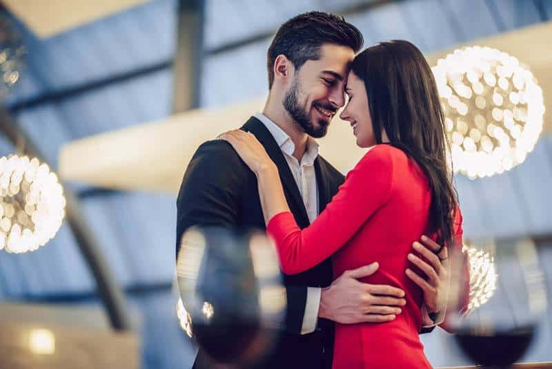 man in suit and woman in red dress hugging