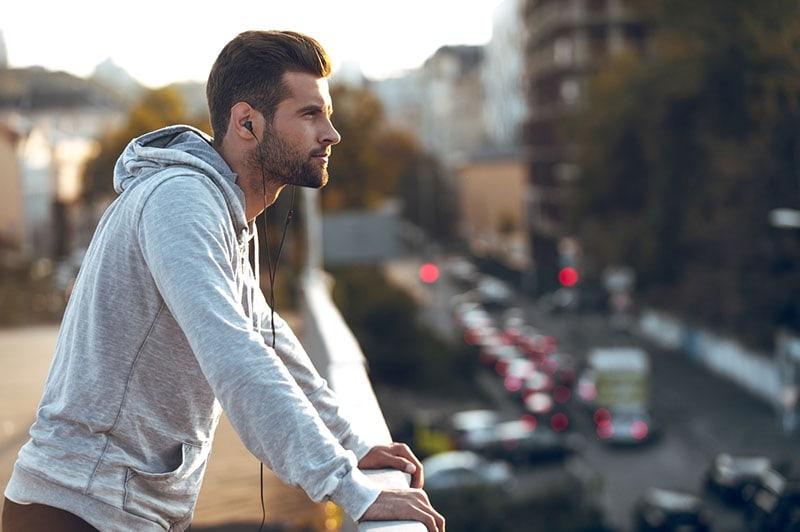 man listens music on earphones