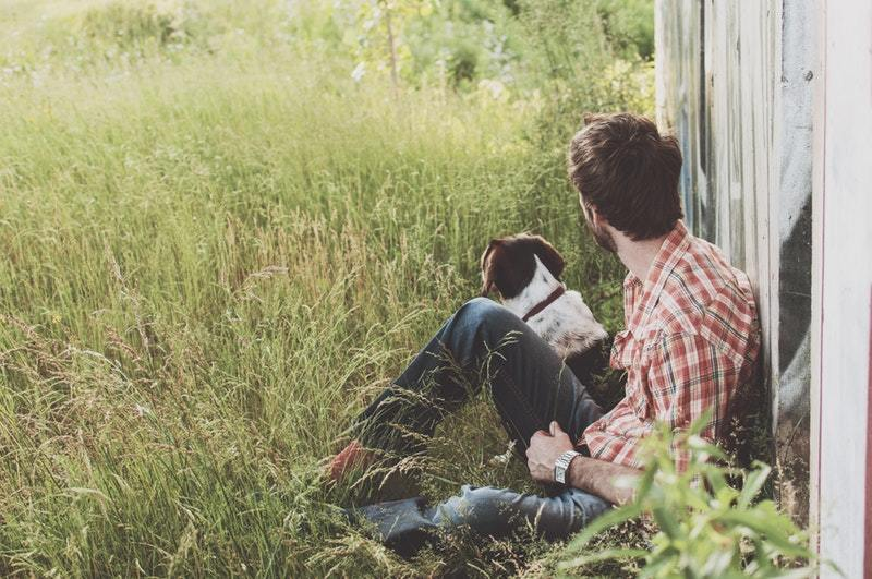man sitting on the grass with dog
