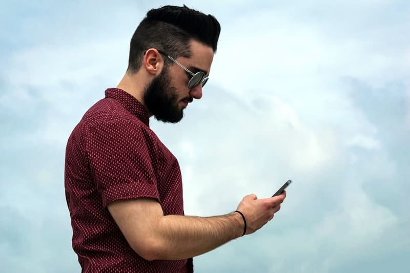 side view of man wearing eyeglasses and looking at his phone
