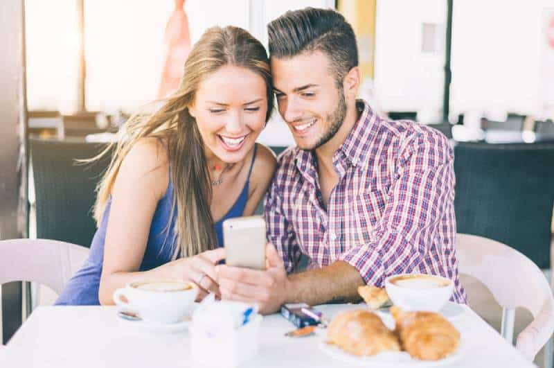 smiling couple in a coffee house having breakfast and looking at phone