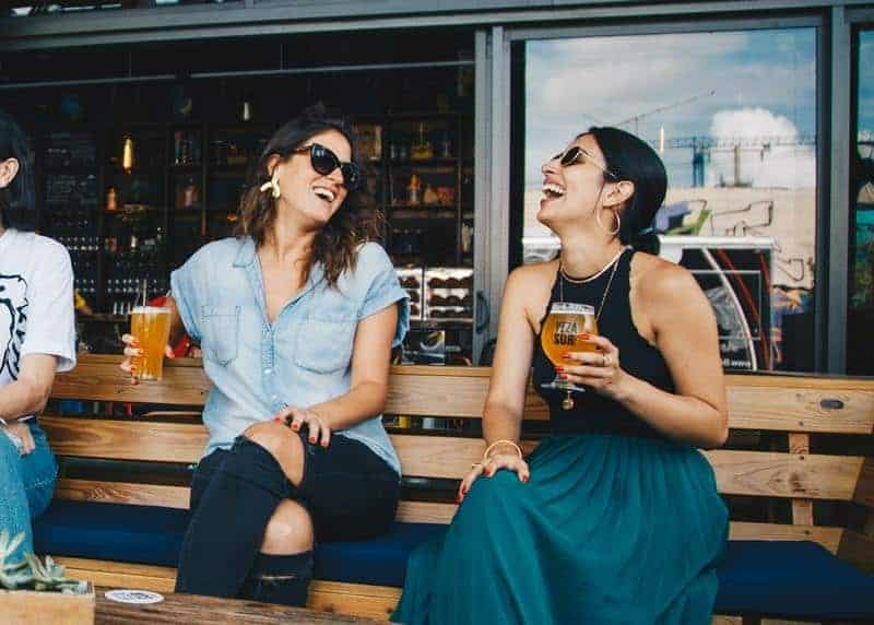 smiling female friends holding a glass of beer