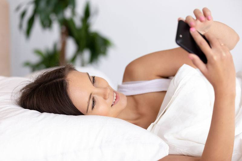 smiling woman holding phone in bed