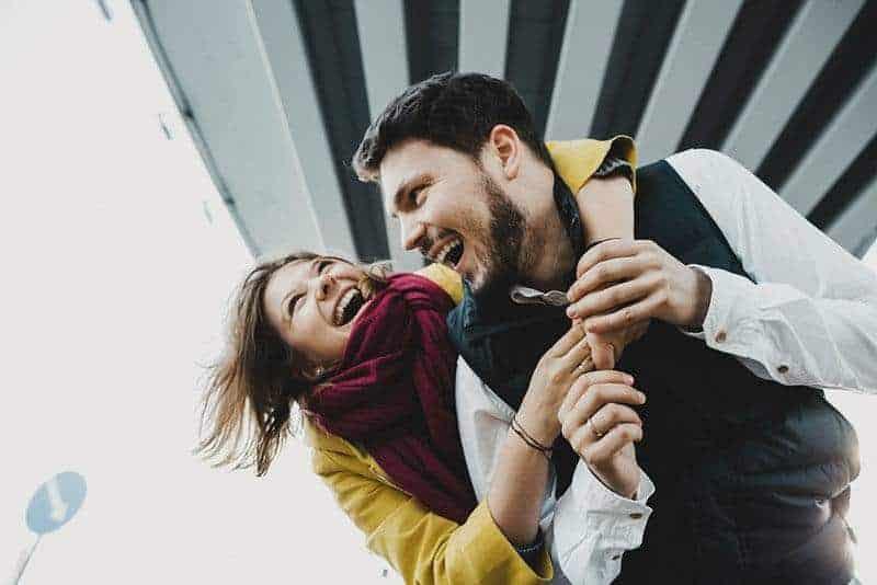 smiling woman hugging man outside
