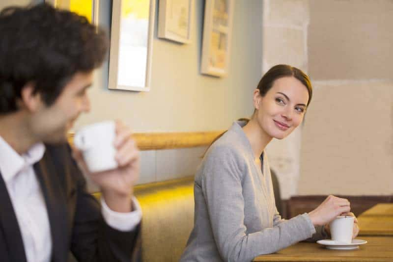 smiling woman looking at man in cafe