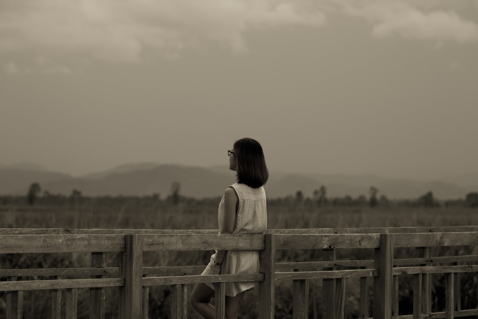 the woman stands leaning against the railing with her back turned