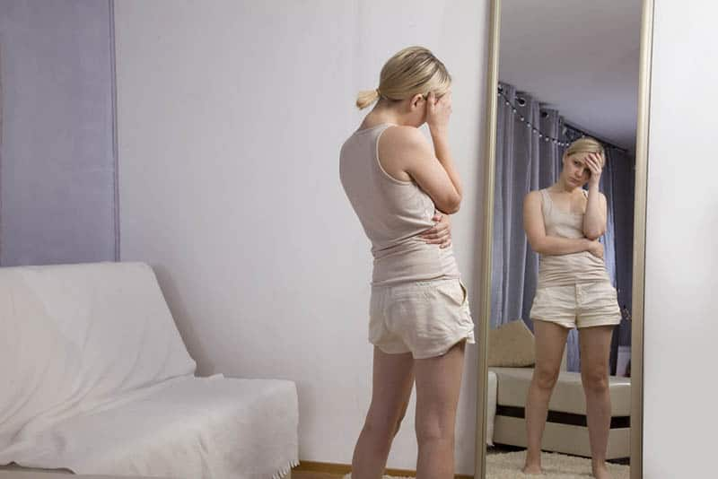 unhappy woman looking herself at mirror