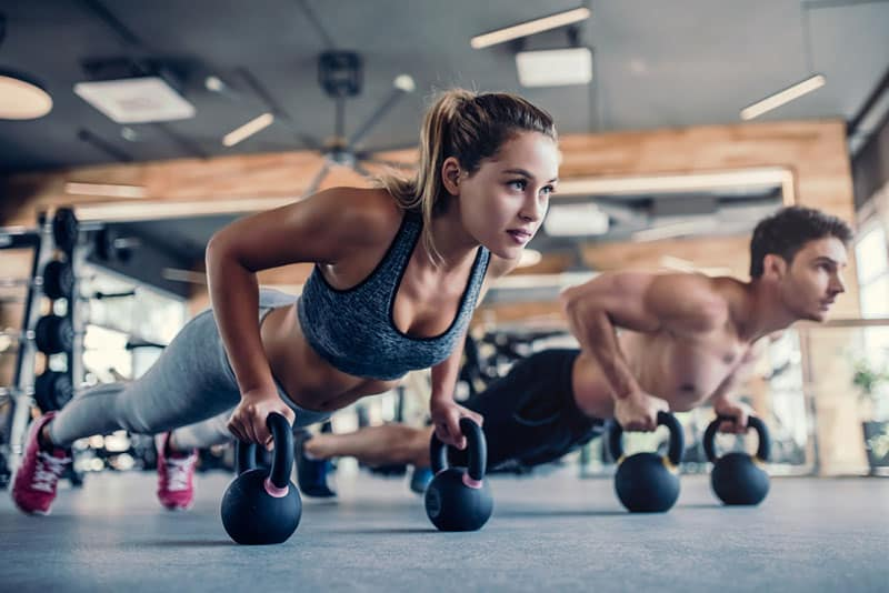 woman and man working out in the gym