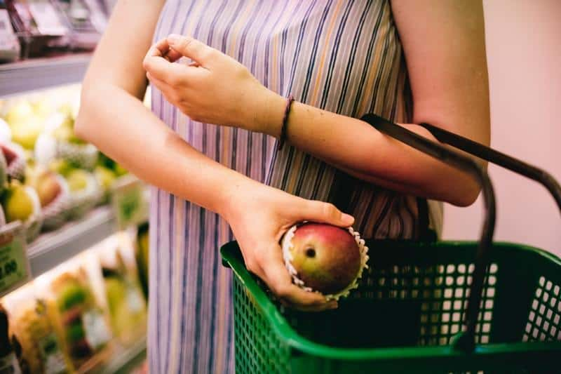 woman buying an apple in the supermarket