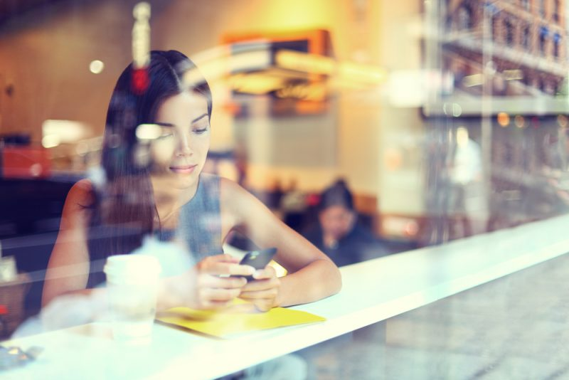 woman drinking coffee and holding her phone