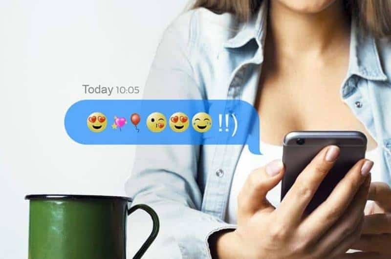 woman holding phone with emoji