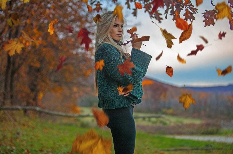 woman posing around brown leafs