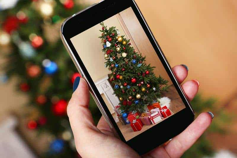 woman taking picture of christmas tree