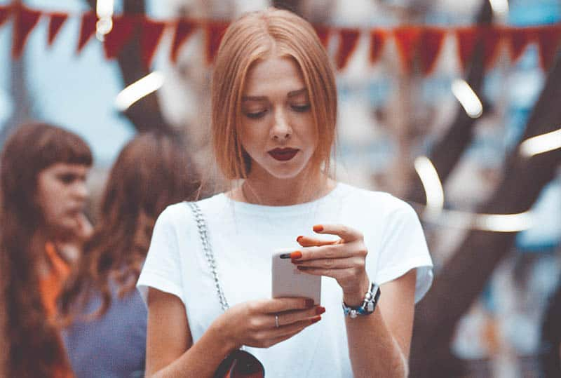 woman wearing white shirt holding her phone