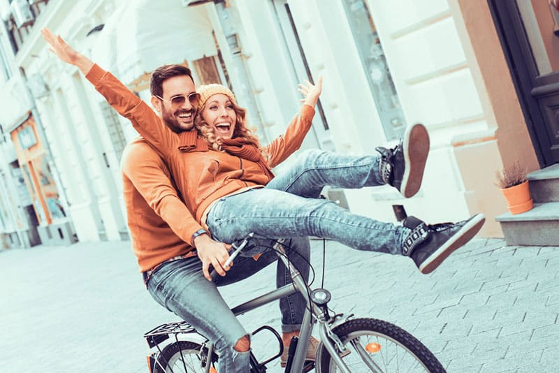 young couple riding on bike