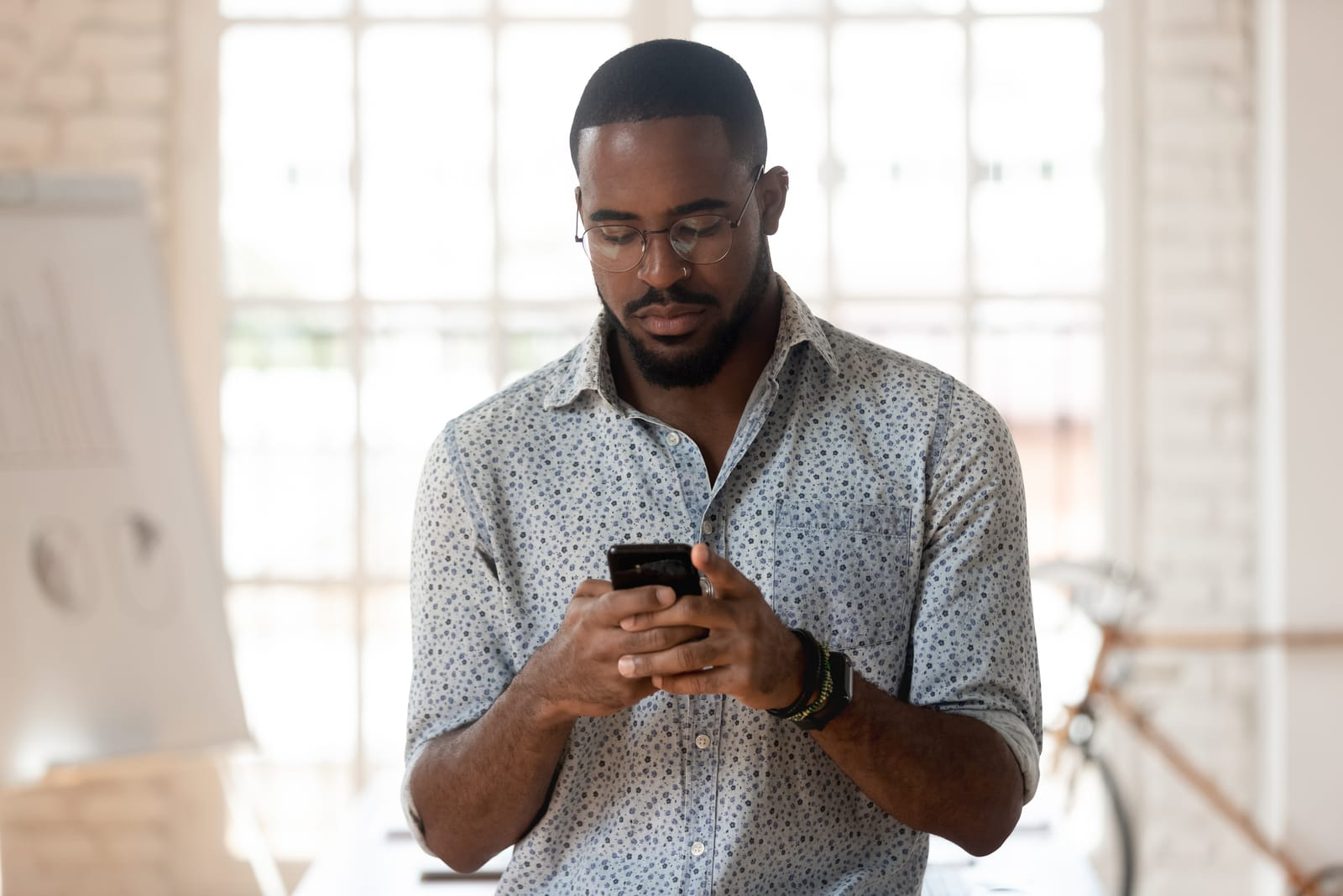 young employee using smartphone at office