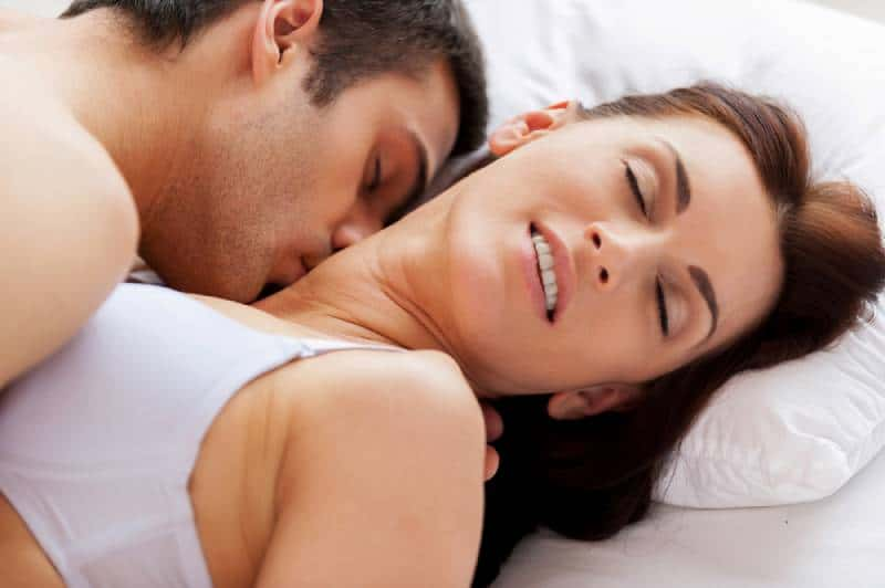 young loving couple making love while lying in bed
