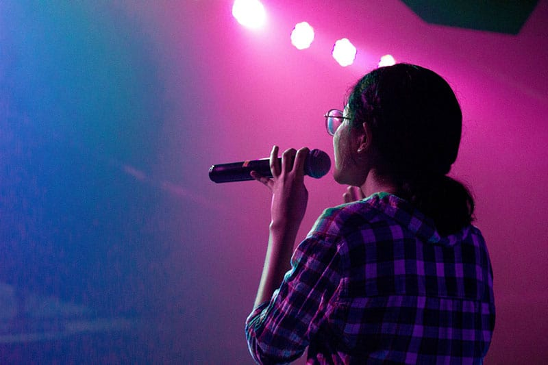 young woman singing karaoke