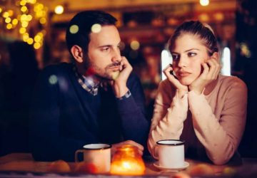 man looking at thoughtful woman in cafe