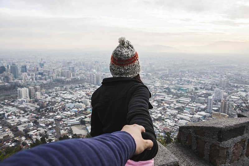 man holds woman's hand from back on city viewpoint