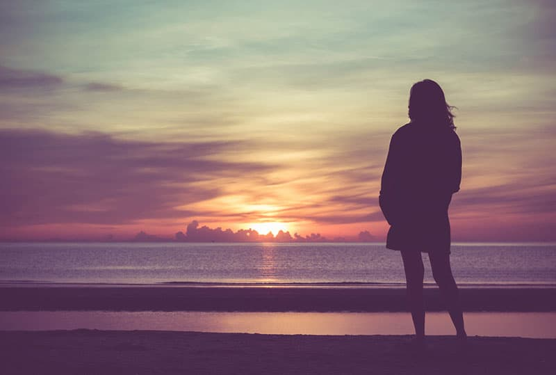 lonely woman watching sunset
