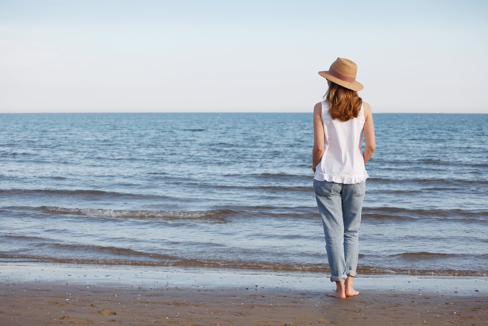 a barefoot woman with a hat standing on the beach by the sea