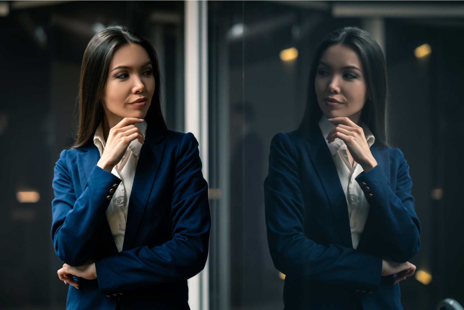 a determined businesswoman looks at herself in the glass with a smile