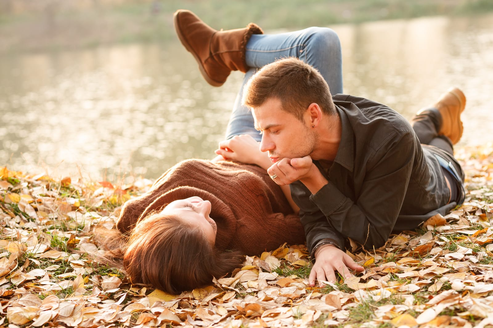 a man and a woman lie on dry leaves in autumn