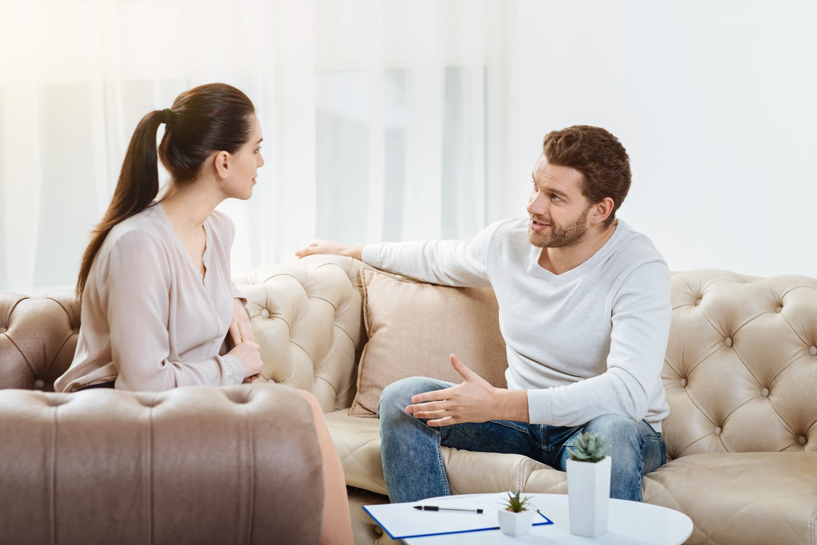 a man with a beard and a woman sitting and talking