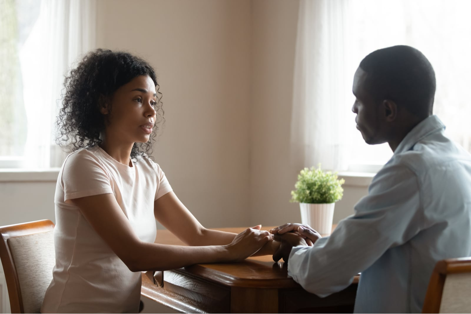 a sad black woman is talking at home with her man