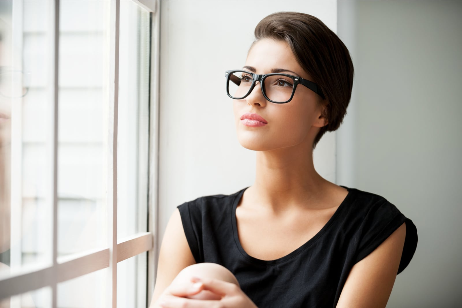 attractive brunette with glasses sitting and thinking