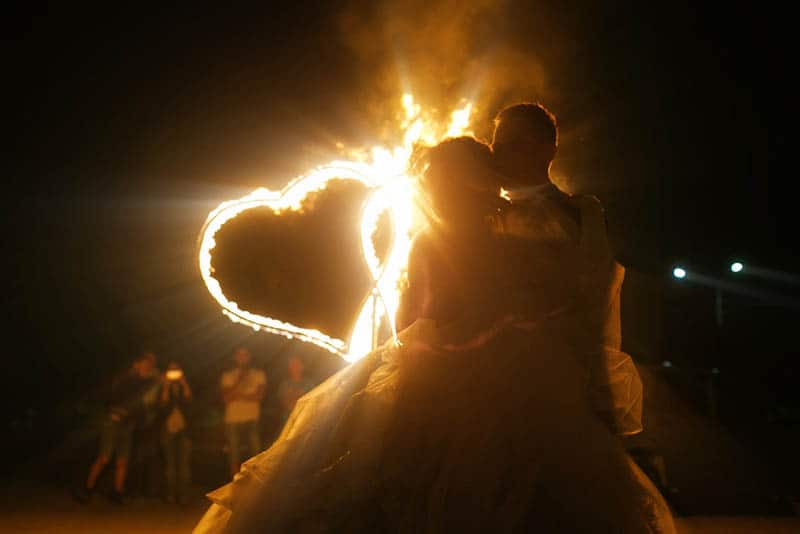 bride hugging while holding fire shape of heart