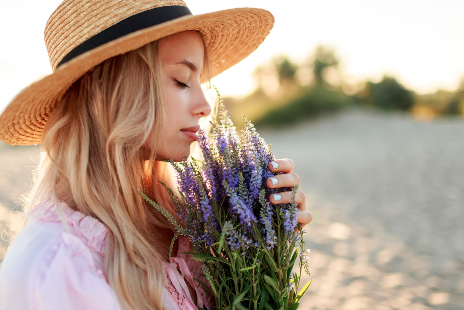 charming blonde girl in straw hat smells flowers on the beach