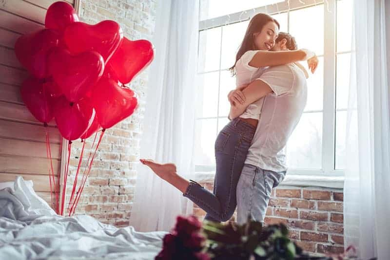 couple hugging at home beside balloons