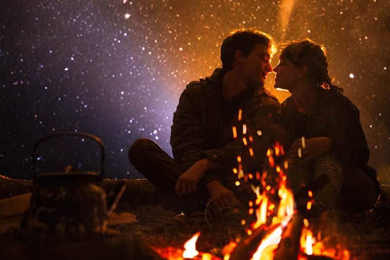 couple sitting in front of bonfire