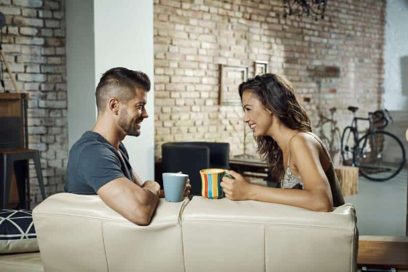 couple sitting in living room and talking with coffee