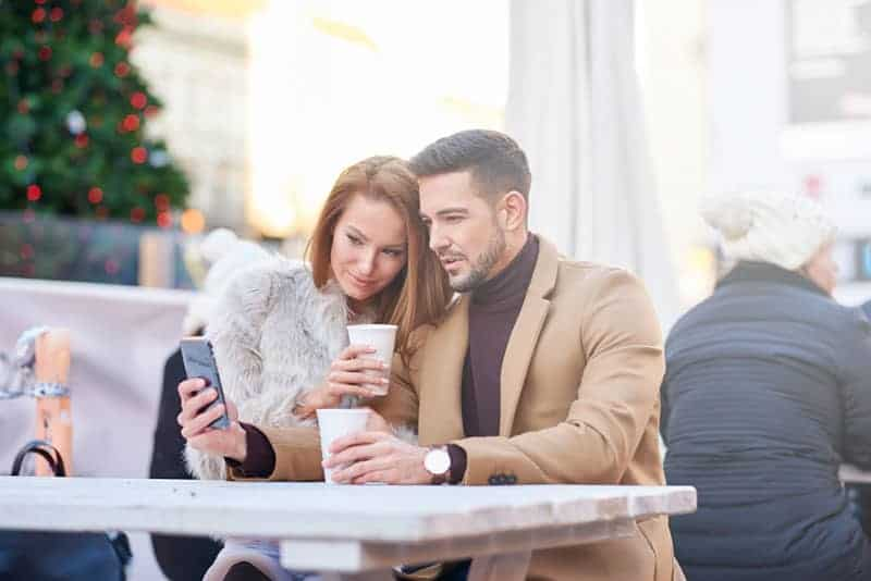 couple sitting in outdoor cafe and looking at smartphone