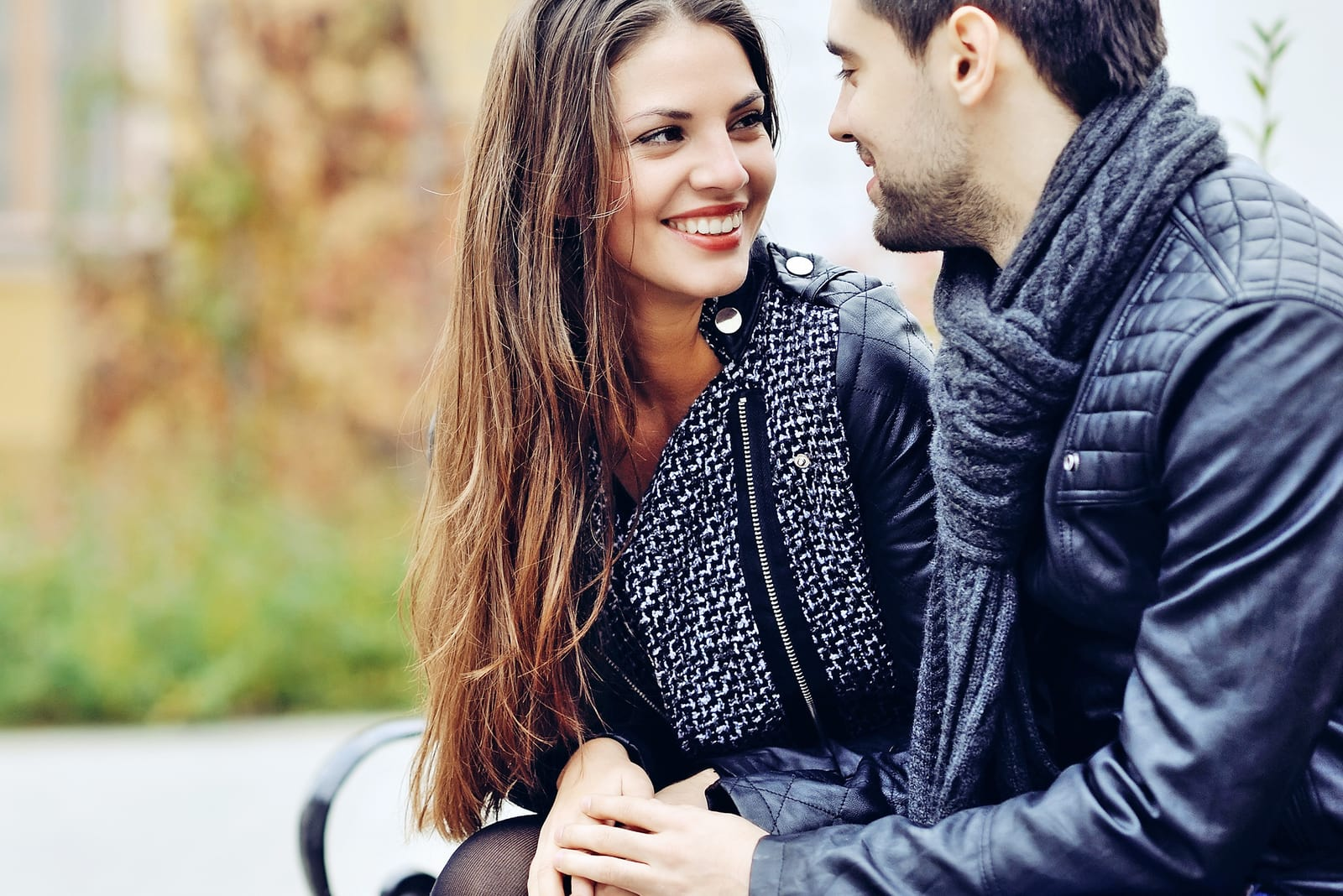 couple smiling and looking each other outdoors
